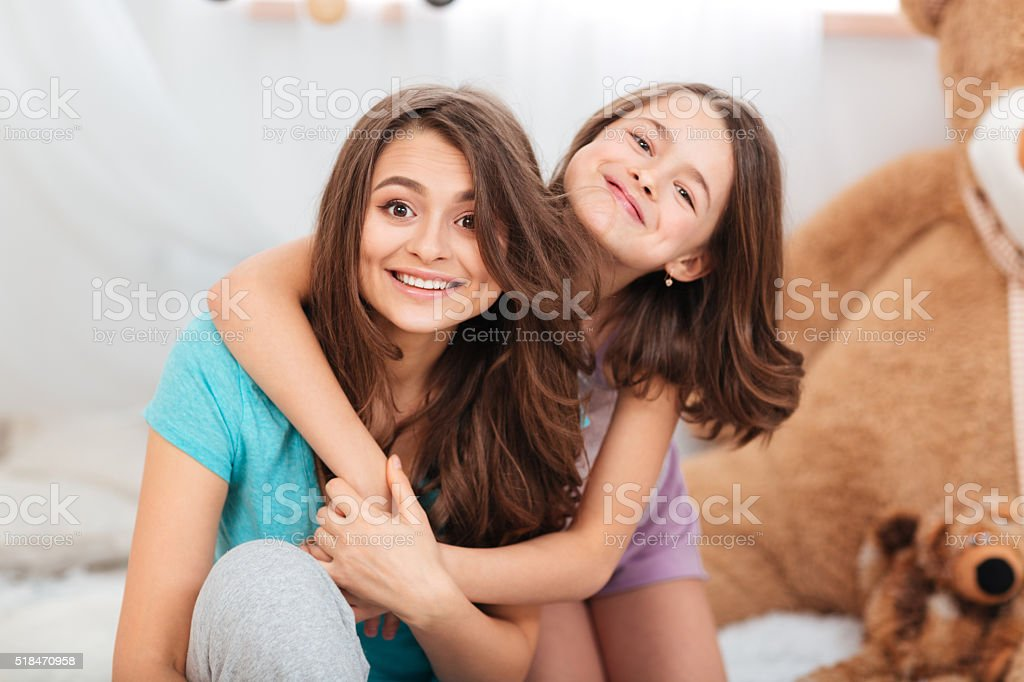 Two happy lovely sisters sitting and hugging at home stock photo