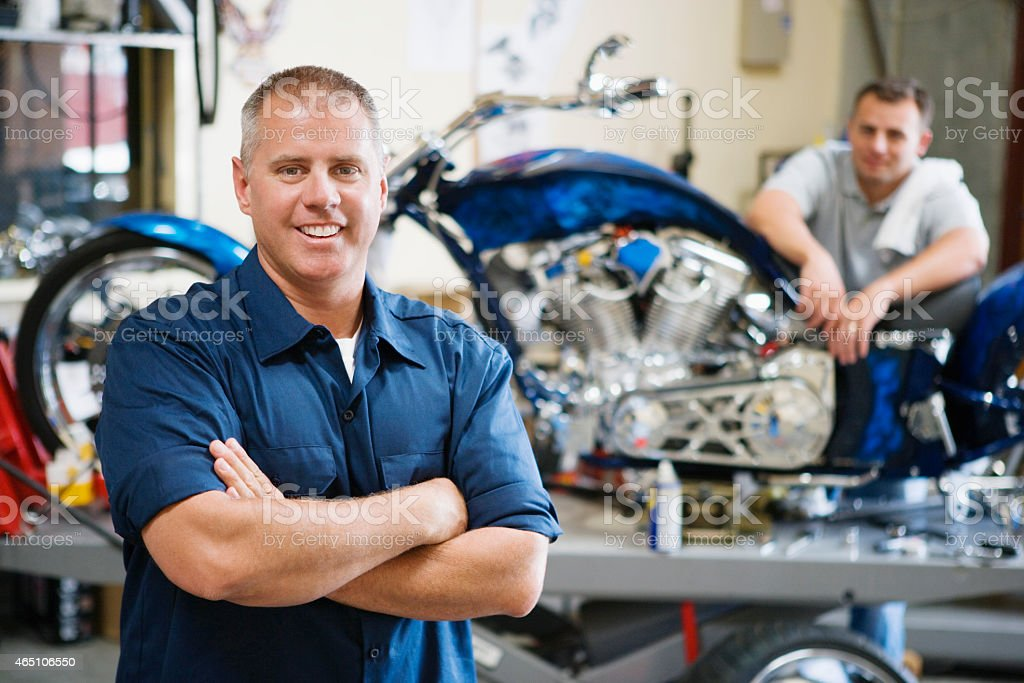 Two Happy Male Mechanics At Workplace stock photo