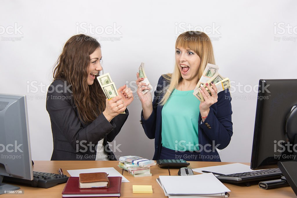 Two happy office girl happy holding wads money their hands stock photo
