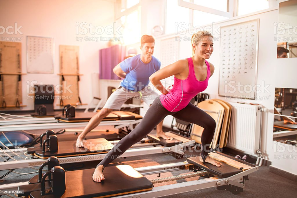 Two happy people exercising on Pilates machines in health club. stock photo
