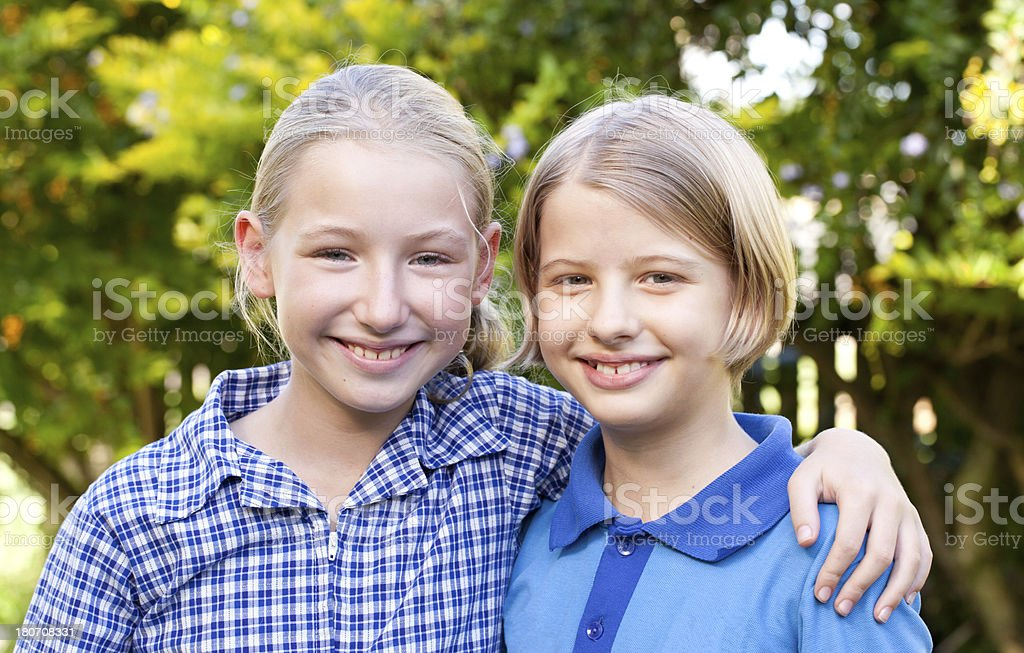 Two happy school girls in uniform with arms around stock photo