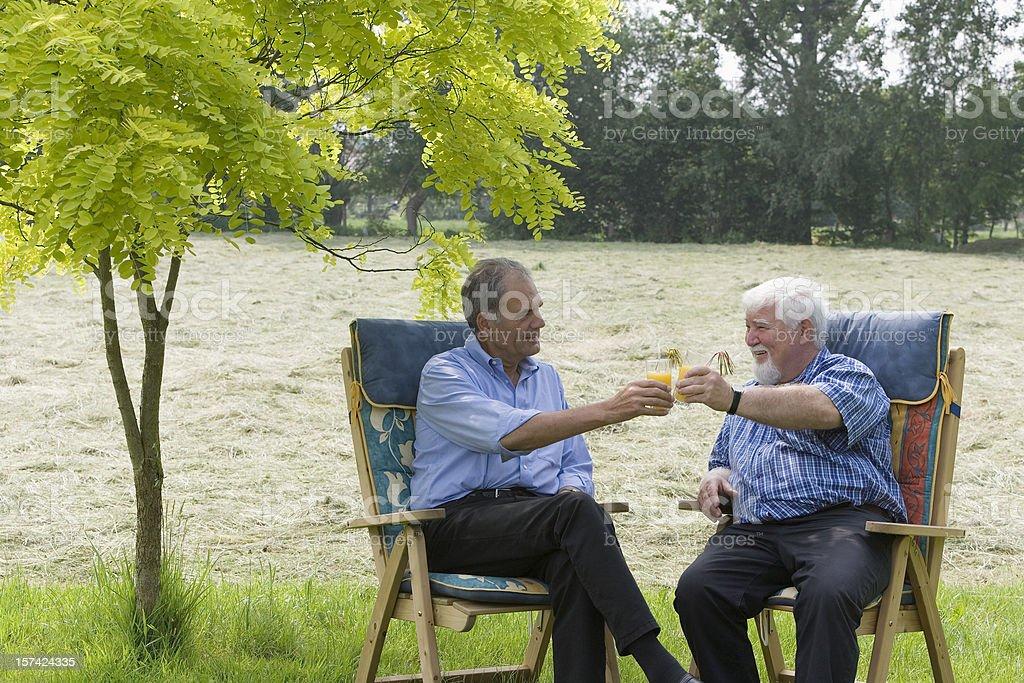 Two happy senior men drinking orange juice outdoors royalty-free stock photo