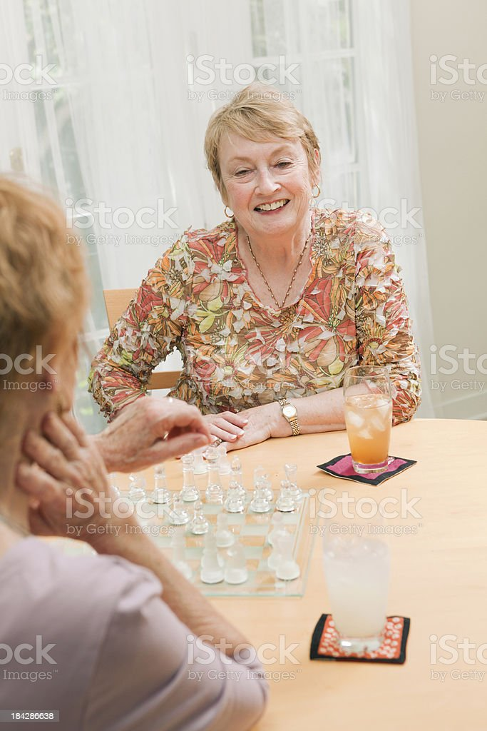 Two Happy Senior Woman Playing Chess in Social Setting royalty-free stock photo