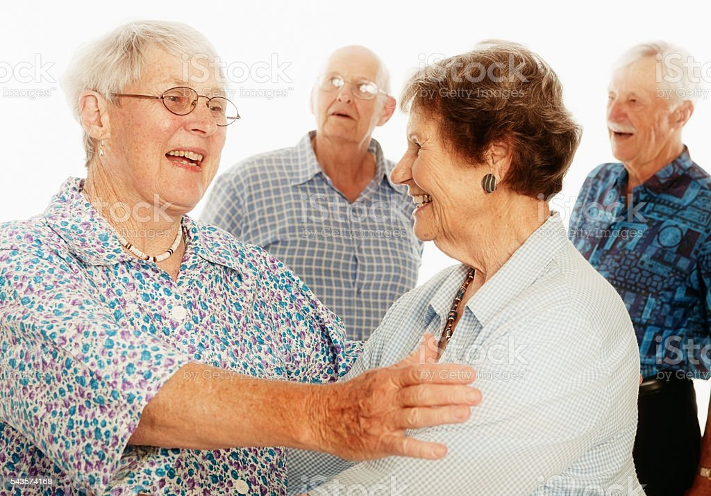 Two happy senior women greet each other, partners in background stock photo