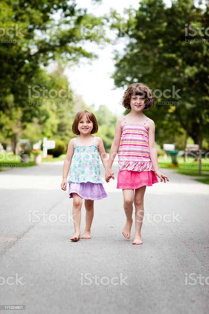 Two Happy Sisters Holding Hands and Walking Outside royalty-free stock photo