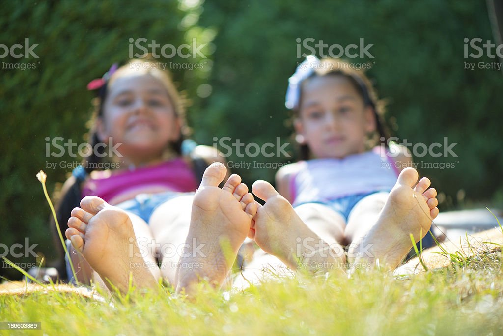 Two happy sisters lying on green grass royalty-free stock photo