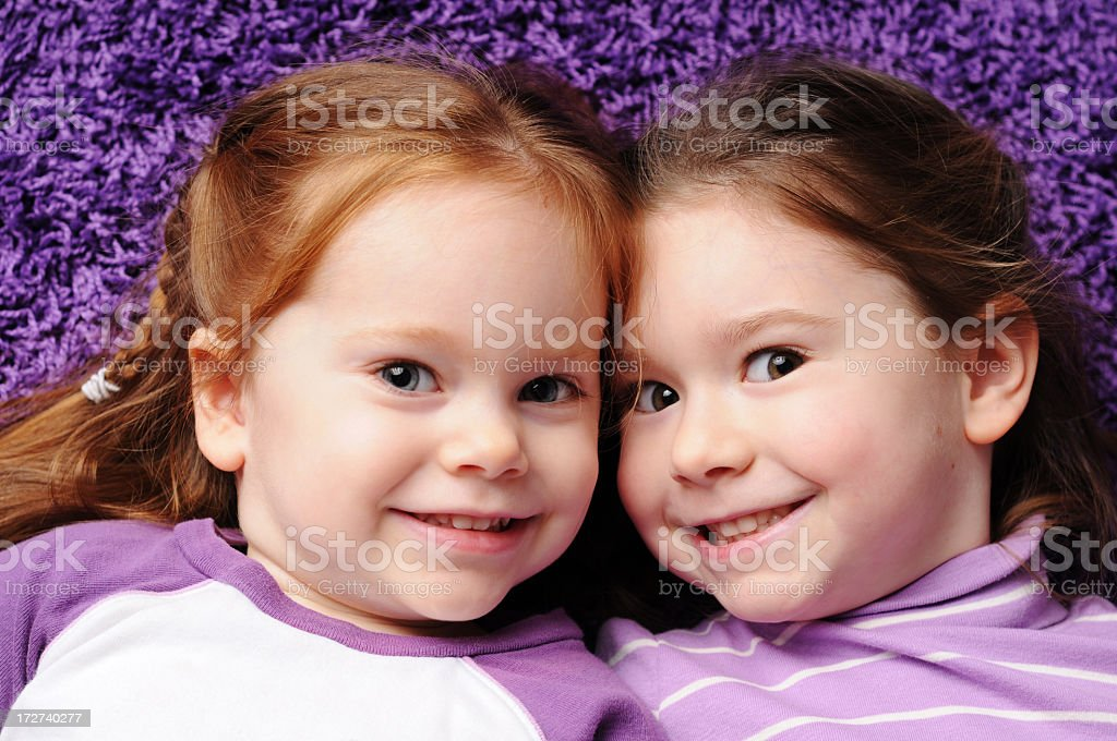 Two Happy Sisters Lying on Purple Carpet royalty-free stock photo