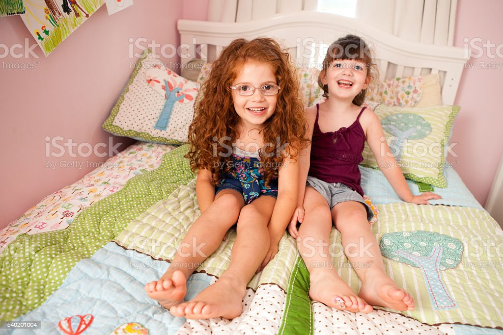 Two Happy Sisters Sitting on Bed in Bedroom stock photo