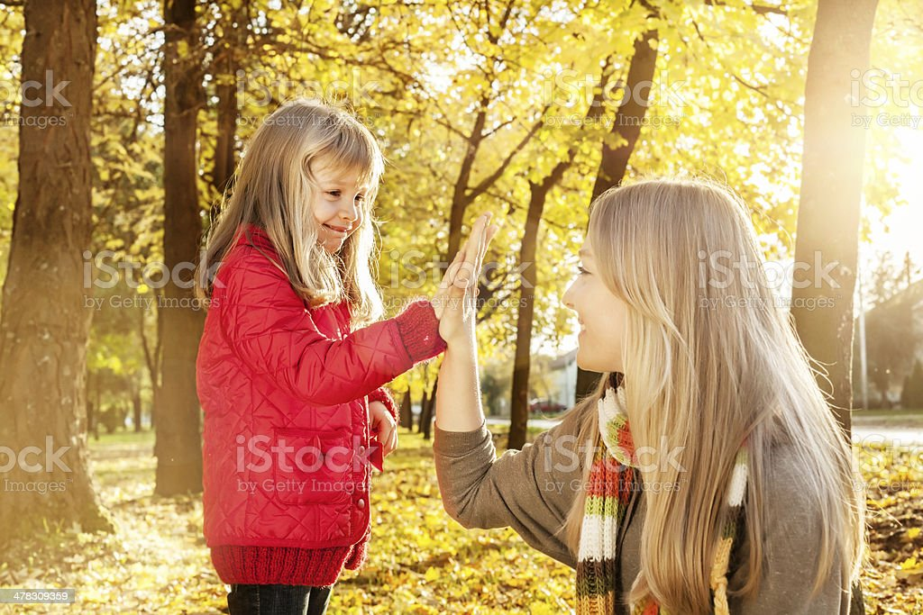 Two happy sisters smiling and giving high five outdoors royalty-free stock photo