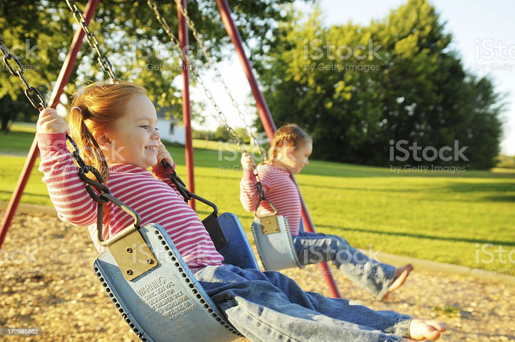 Two Happy Sisters Swinging Together royalty-free stock photo