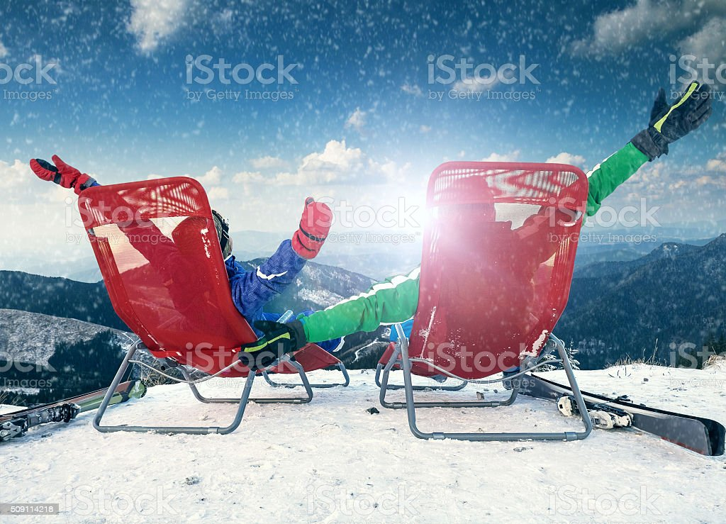 Two happy skiers on the top of mountain stock photo