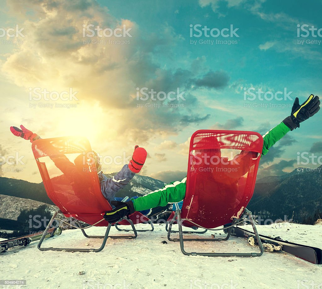 Two happy skiers sitting in chaise-longues on mountain peak stock photo