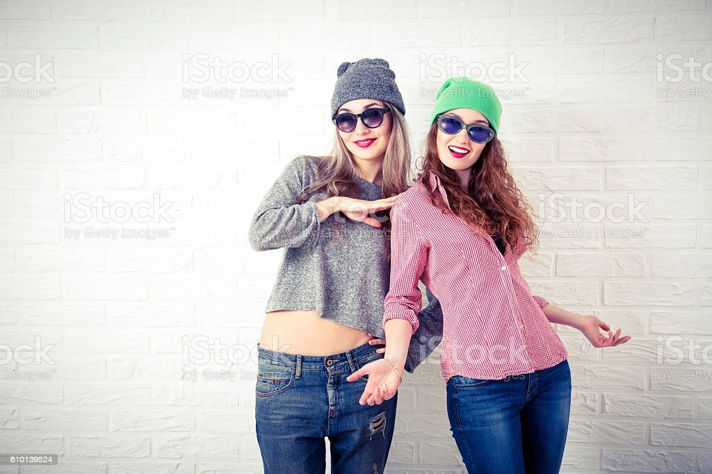 Two Happy Smiling Hipster Girls at White Wall stock photo