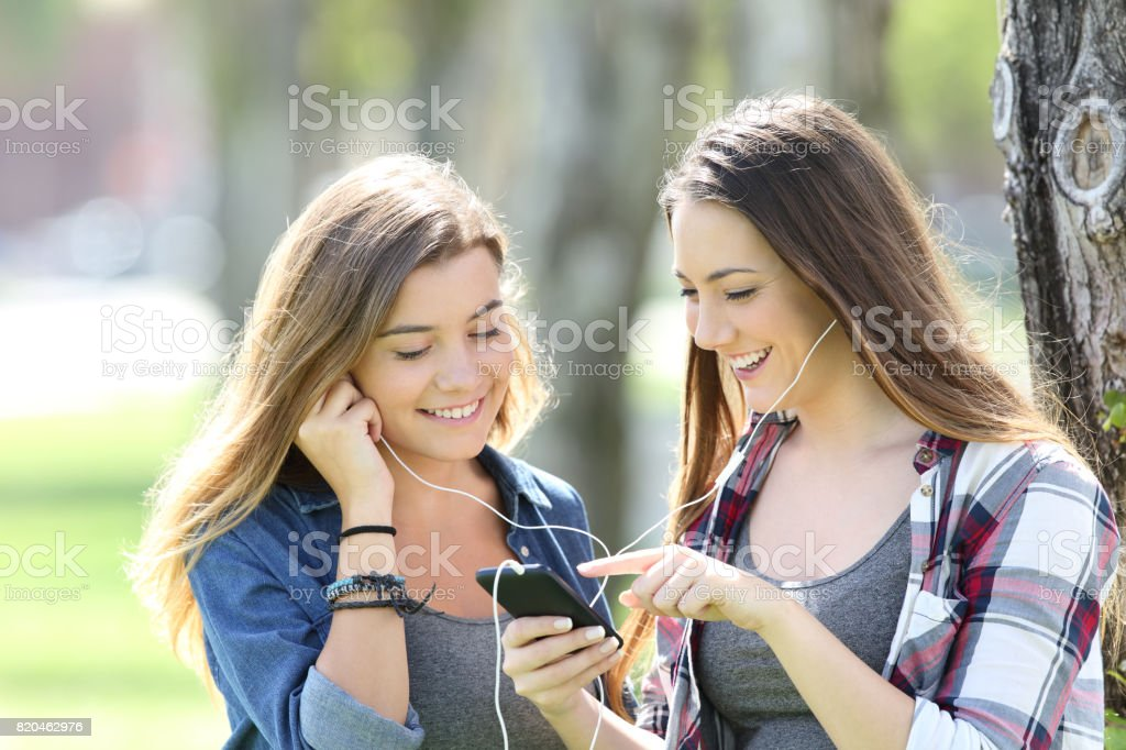 Two happy teen friends listening music stock photo