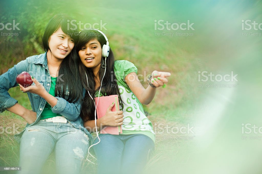Two happy teenage girls from different ethnicity together in nature. stock photo