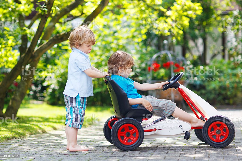 Two happy twin boys driving toy car stock photo