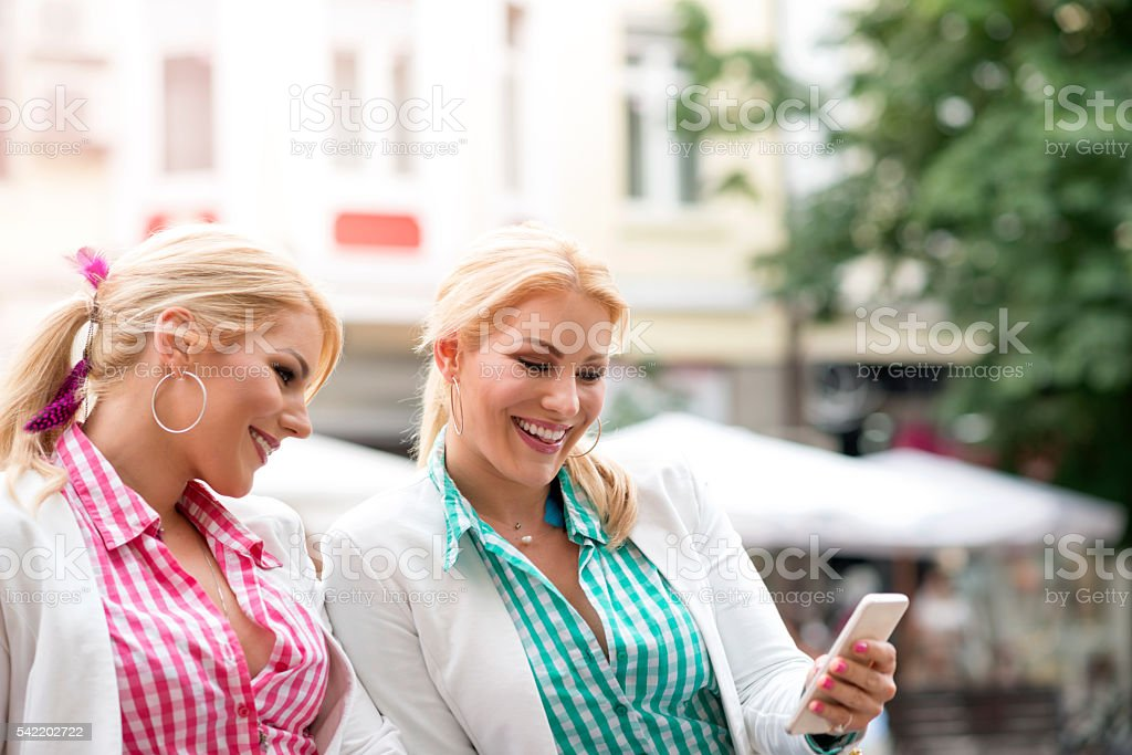 Two happy twin sisters sharing social media in a smartphone stock photo