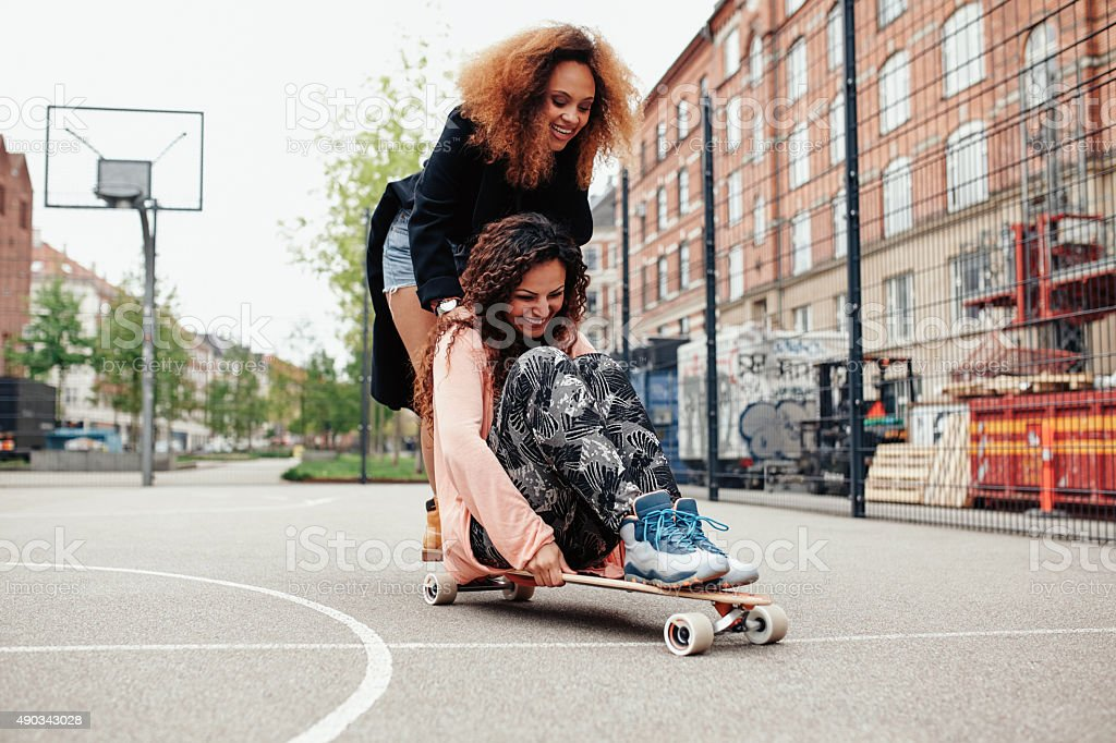 Two happy women having fun skating stock photo