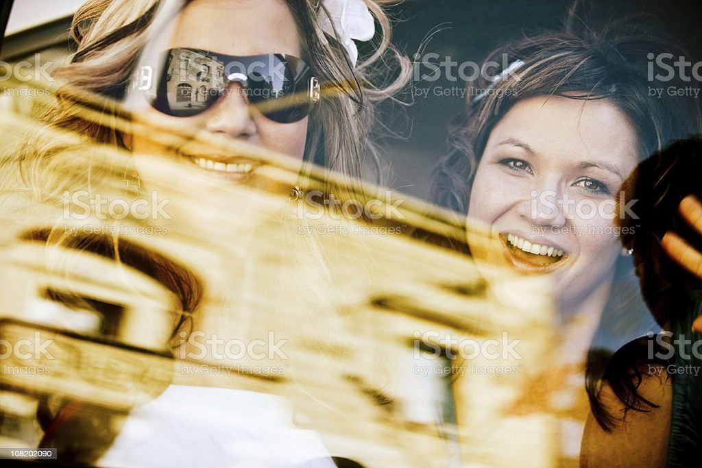 Two Happy Women in Car with Scenery Reflection on Window royalty-free stock photo