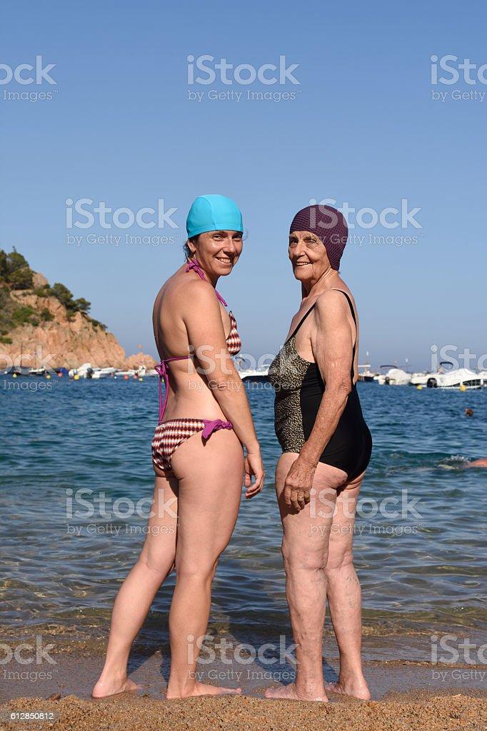 Two happy women on the beach stock photo
