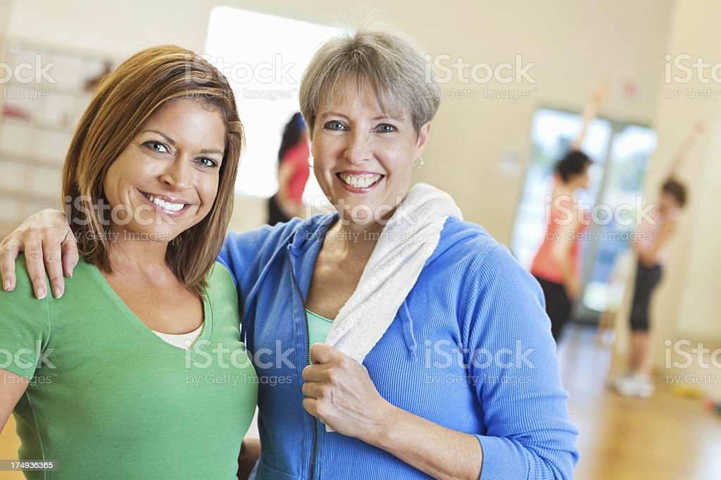 Two happy women posing in exercise fitness class stock photo