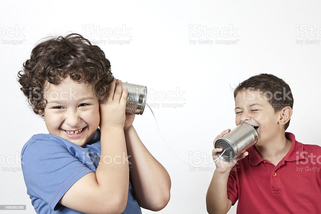 Two happy young boys using tin cans and a string as a phone stock photo