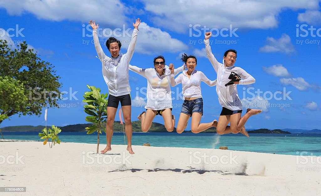 Two happy young couples jump on tropical white beach royalty-free stock photo