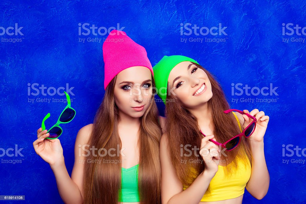 Two happy young girlfriends in color hats holding glasses stock photo