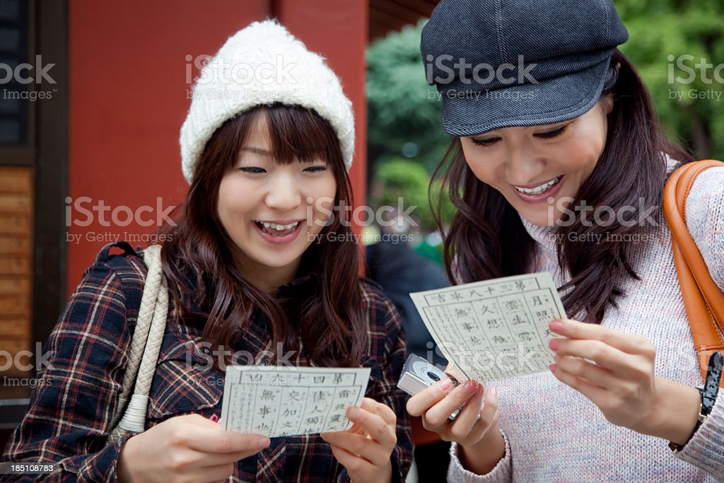 Two happy young Japanese women reading omikuji fortune papers stock photo