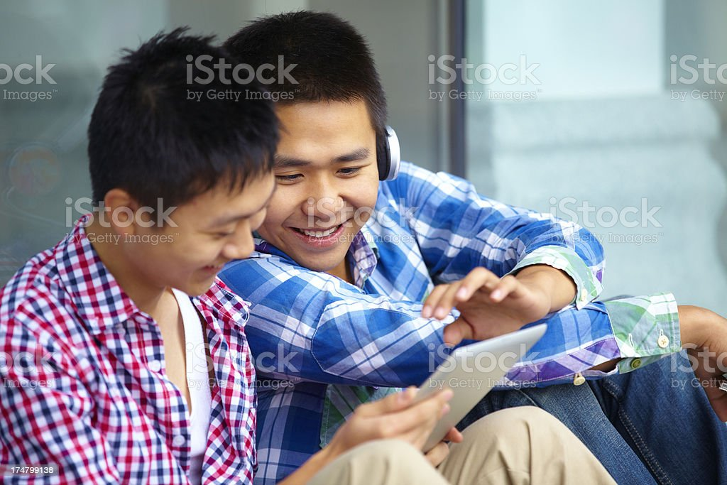 two happy young men using tablet together royalty-free stock photo