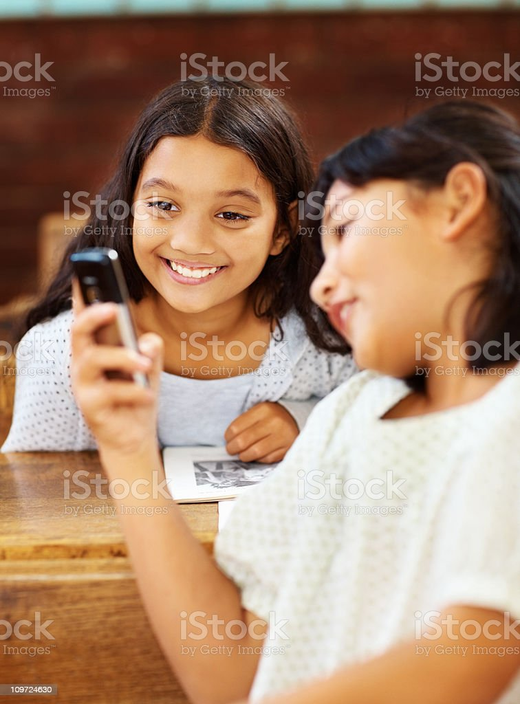 Two happy young school girls with a cellphone royalty-free stock photo