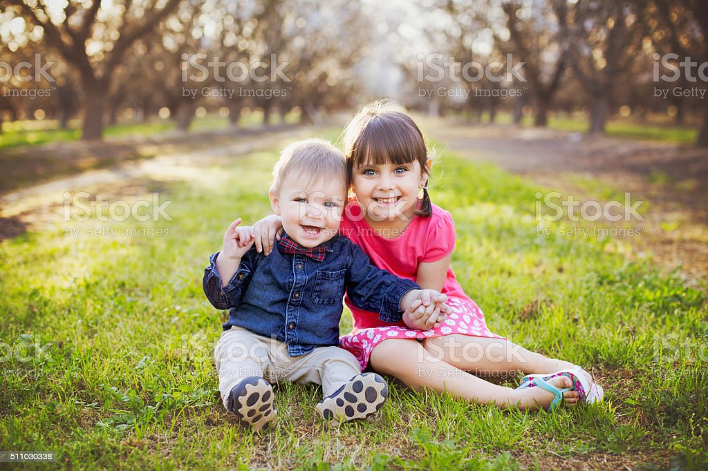 Two Happy Young Siblings are Bonding at the Almond Orchards stock photo