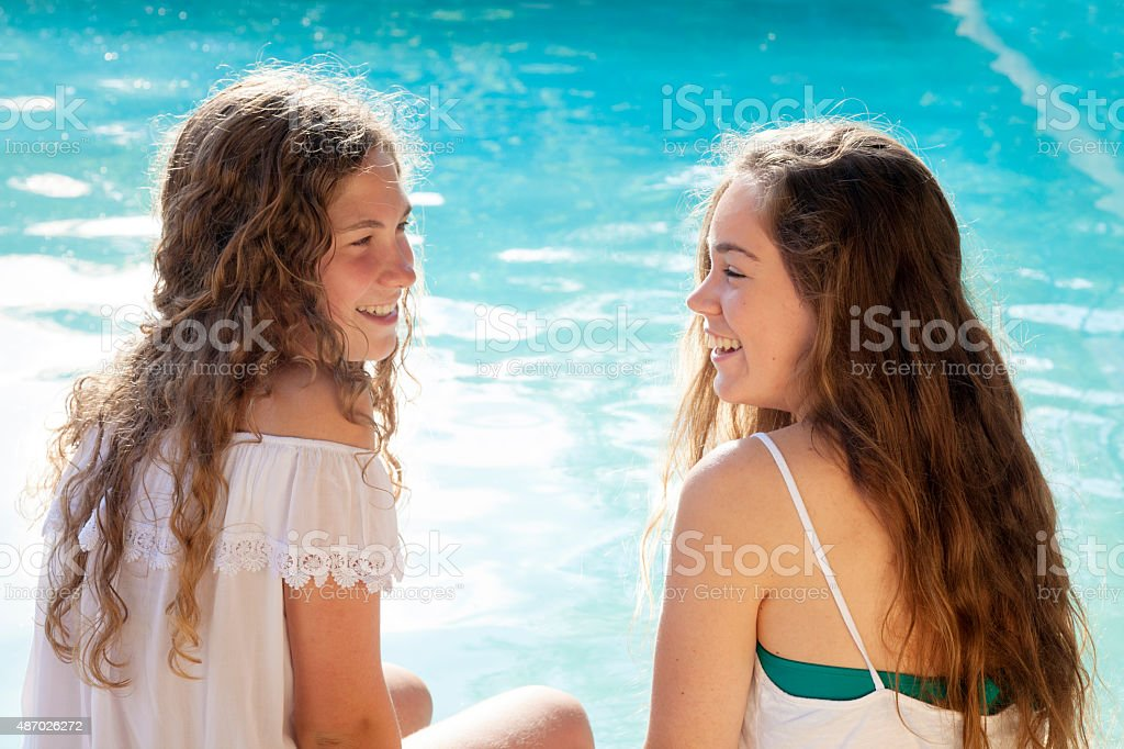 Two happy young woman in the swimming pool stock photo