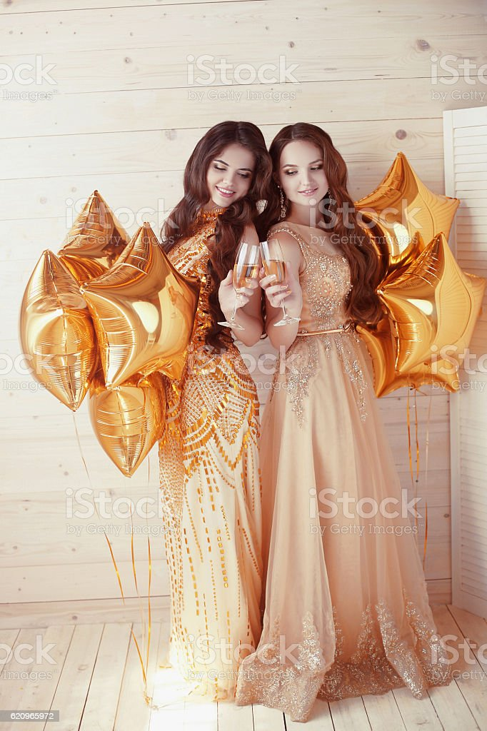 Two happy young women on party with glasses of champagne. stock photo