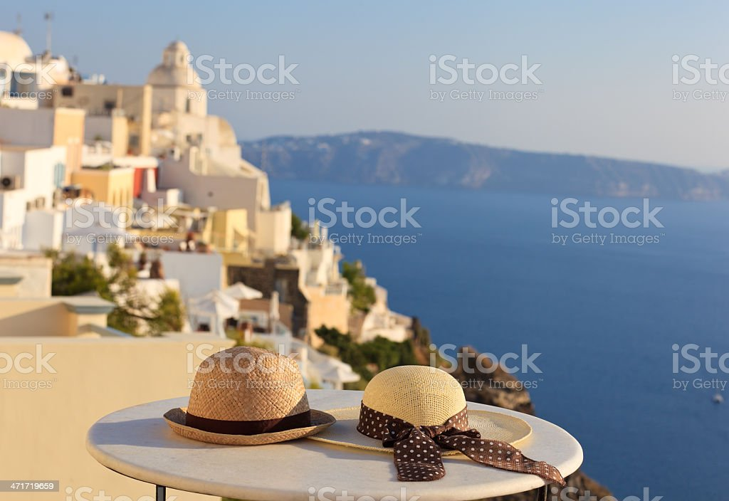 Two hats on a table against the Satorini coastline royalty-free stock photo