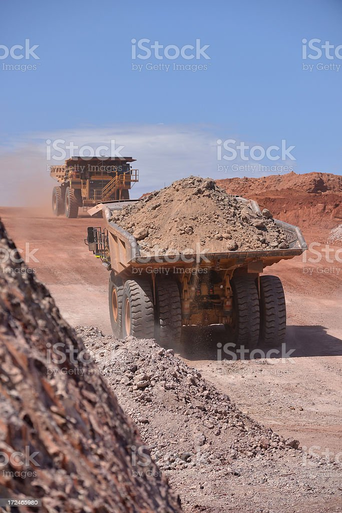 Two haul trucks driving along a road on a minesite. stock photo