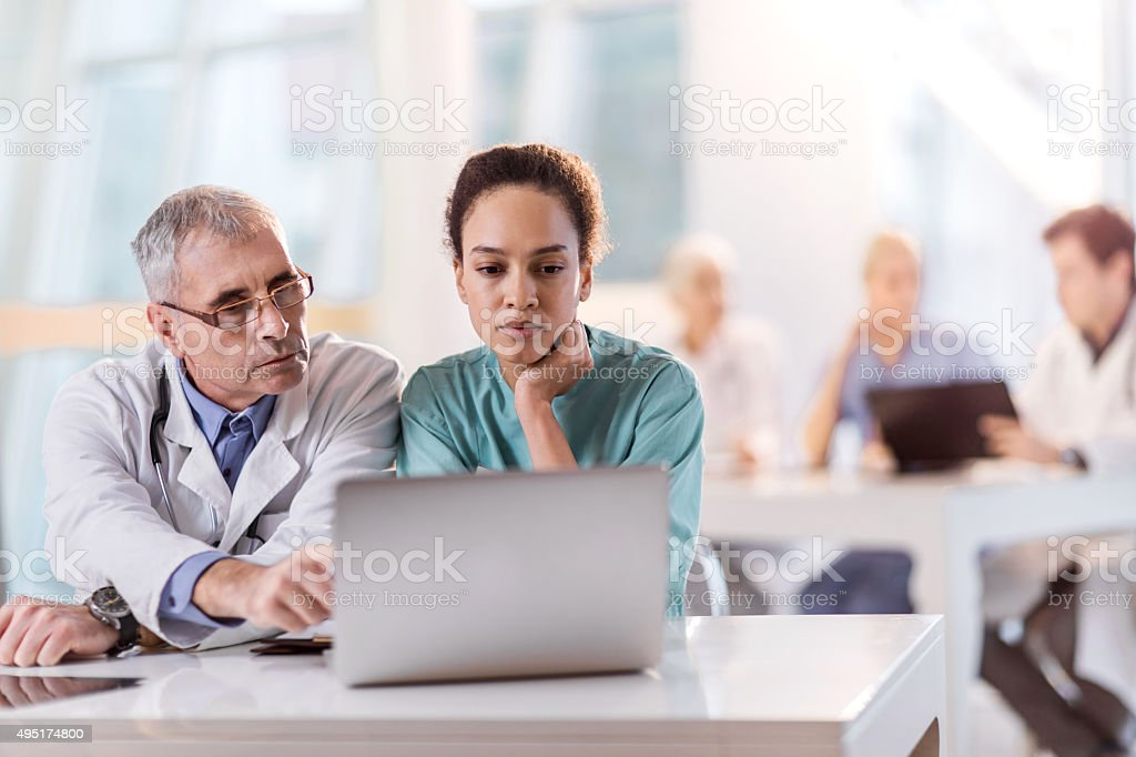Two healthcare workers working together on a laptop. stock photo