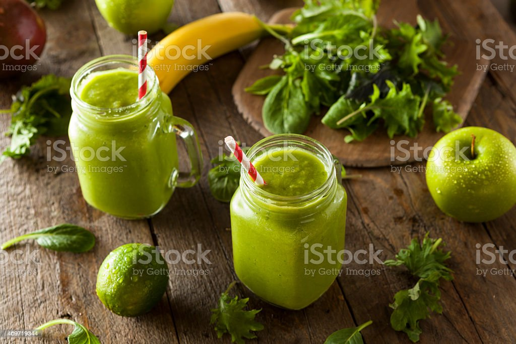 Two healthy green smoothies on wooden table stock photo