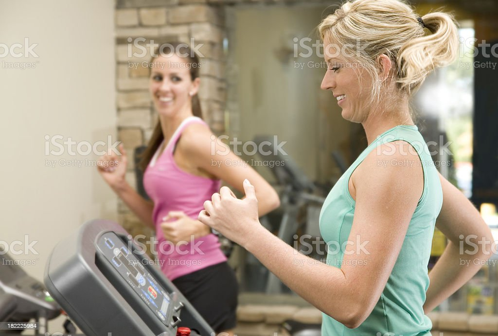 Two Healthy Women Running on Treadmills at a Fitness Center royalty-free stock photo