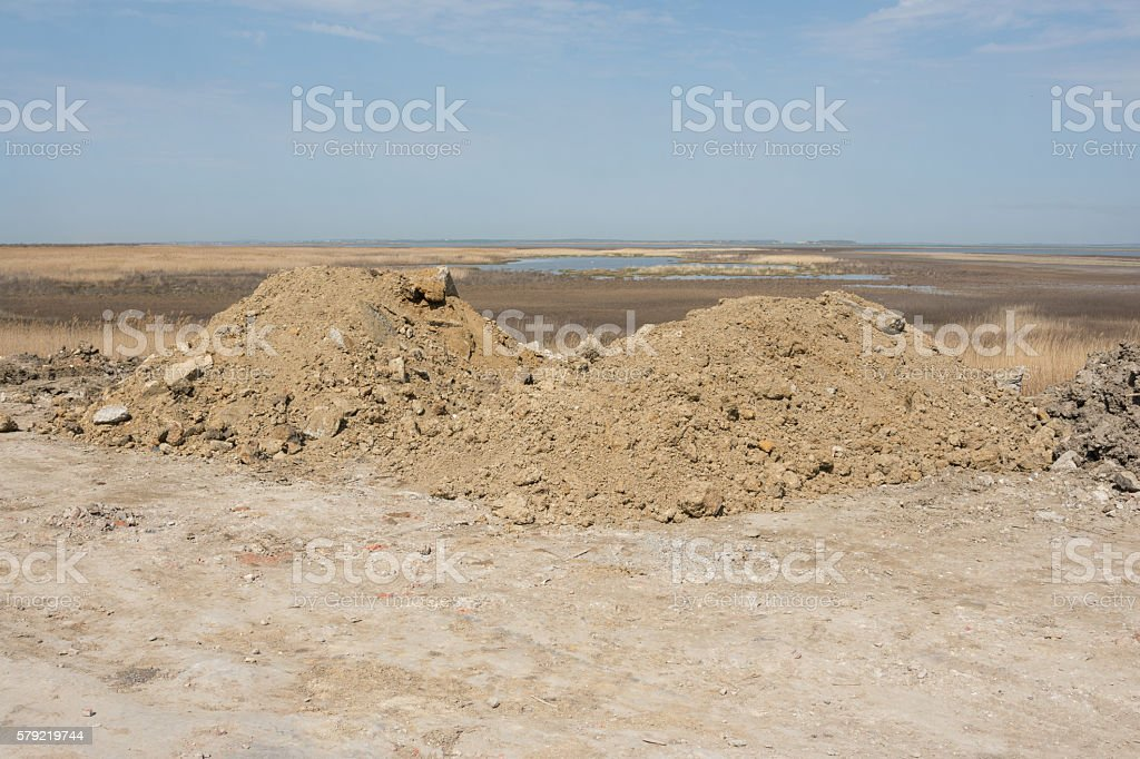 Two heaps of earth with small amount construction waste stock photo