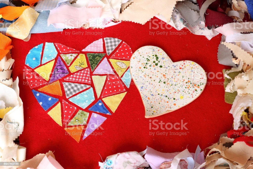 Two heart. Ceramic and textile of multicolored embroidered patches on red cloth on multi-colored pieces of fabric background. Love, romance and creativity stock photo