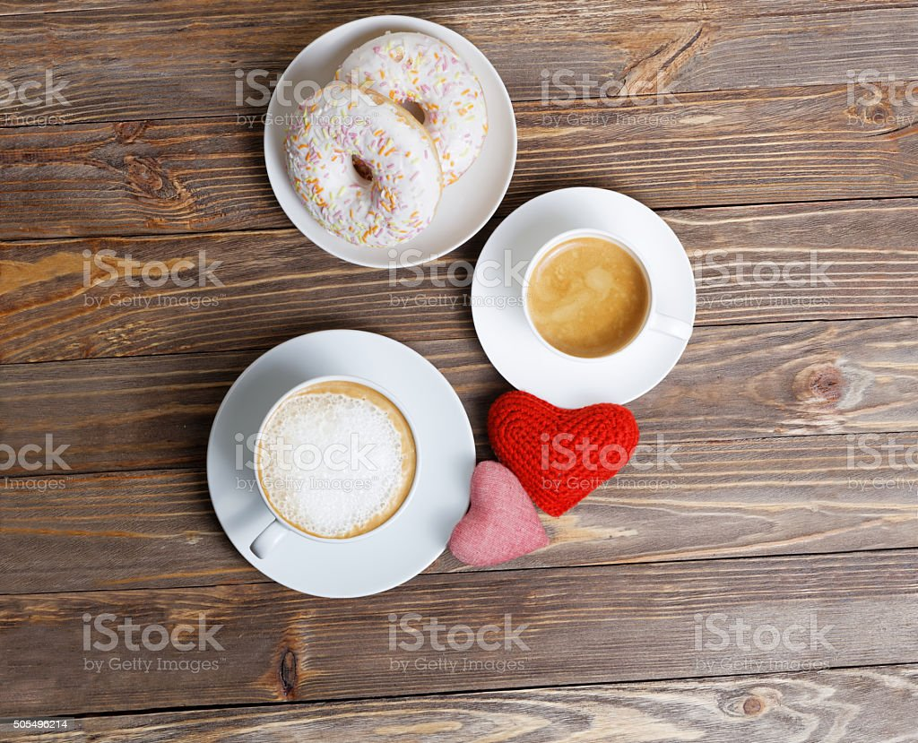 Two hearts and two cups of cappuccino and espresso stock photo