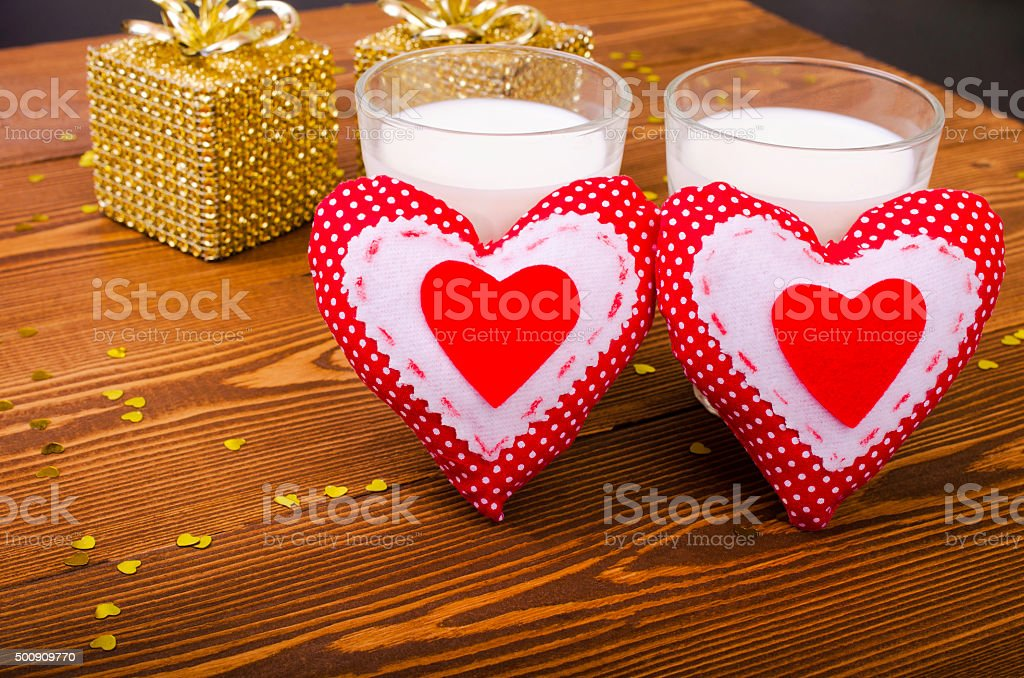 Two hearts and two golden gift and two glasses of milk on wooden...