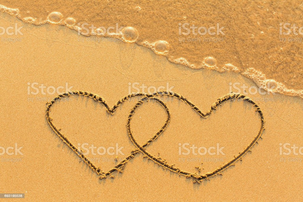 Two hearts drawn in the sea sand with the soft wave. stock photo