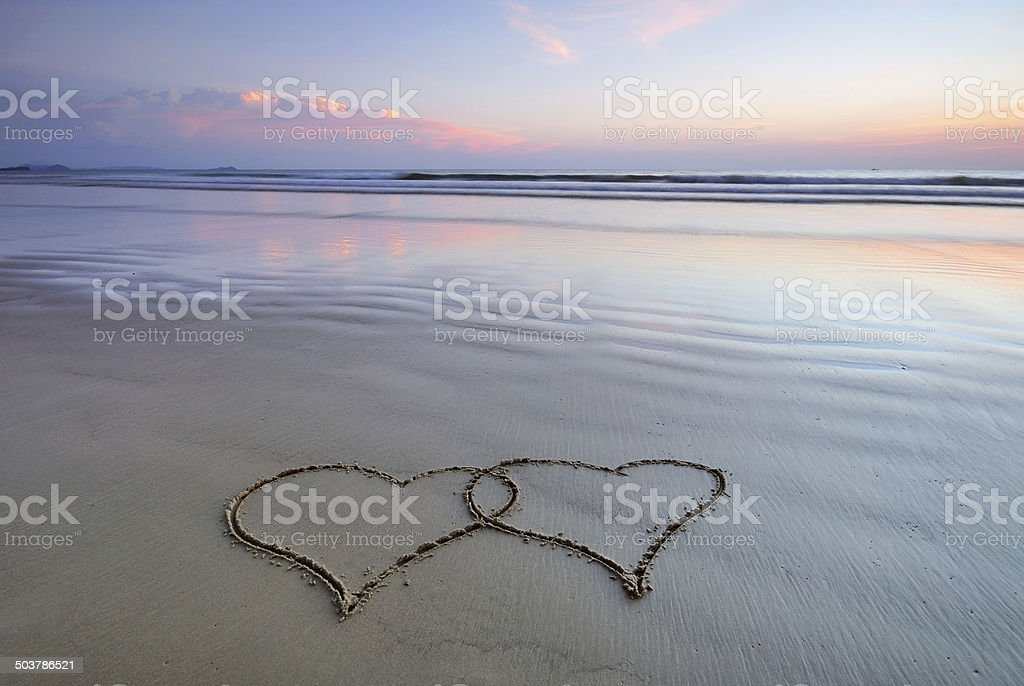 Two hearts drawn on beach sand stock photo