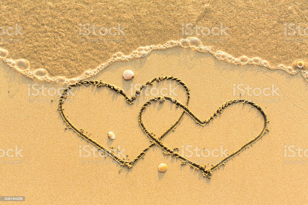 Two hearts drawn on the sand of a beach. stock photo