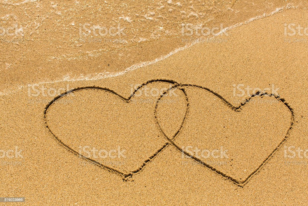 Two hearts drawn on the sand of a sea beach. stock photo