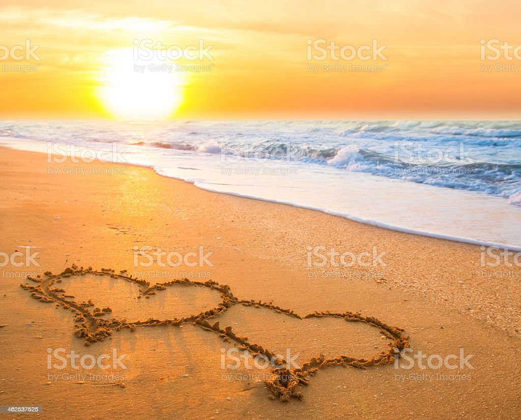 Two hearts etched together on sandy beach at susnet stock photo