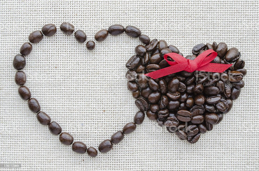 Two hearts of coffee beans on a textured bag royalty-free stock photo