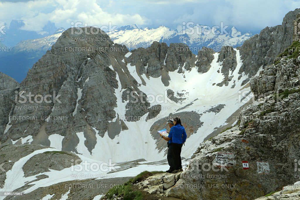 Two hikers are checking trekking map, mountain panorama in background stock photo